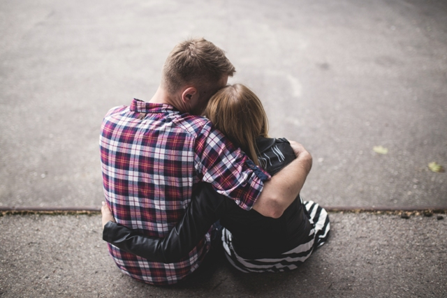 Man hugging girl on concrete