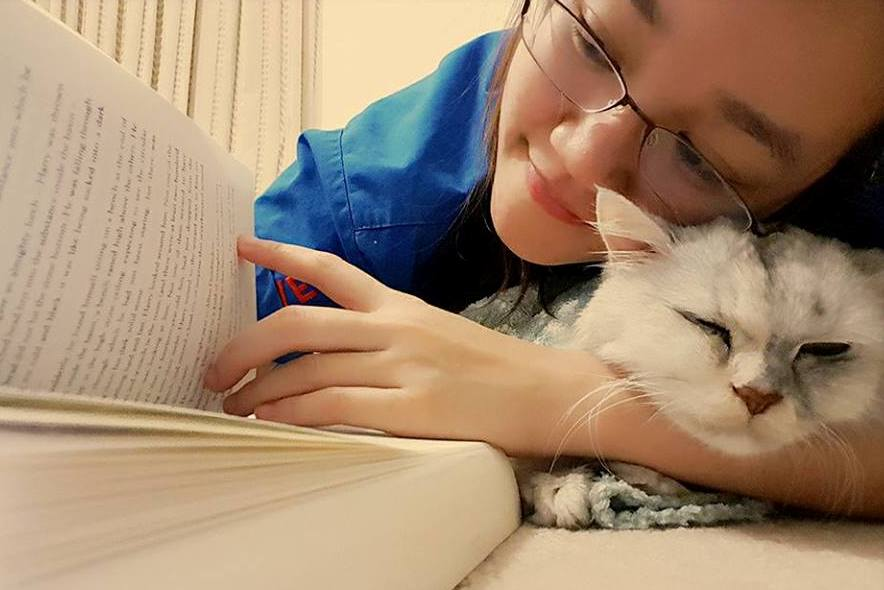 ARH vet, Dr Cindy, reading a book with her white cat